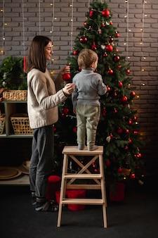 Madre e figlio che decorano l'albero di natale