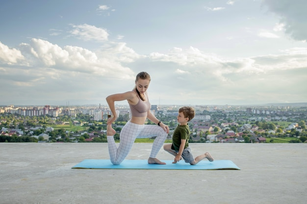 Mother and son doing exercise on the balcony in the background of a city during sunrise or sunset, concept of a healthy lifestyle.