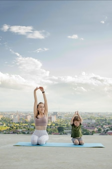 Mother and son doing exercise on the balcony in the of a city during sunrise or sunset, concept of a healthy lifestyle.