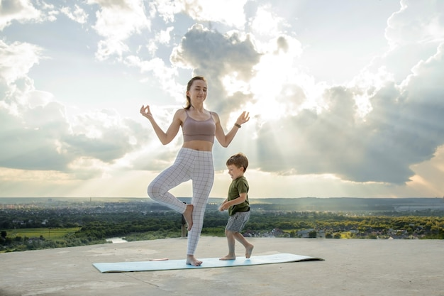 Mother and son doing exercise on the balcony in the of a city during sunrise or sunset