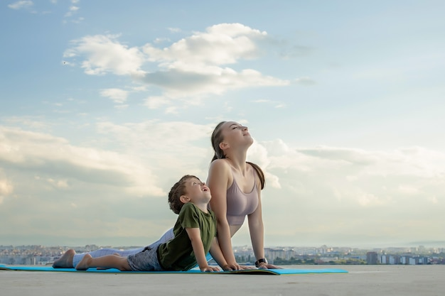Mother and son doing exercise on the balcony