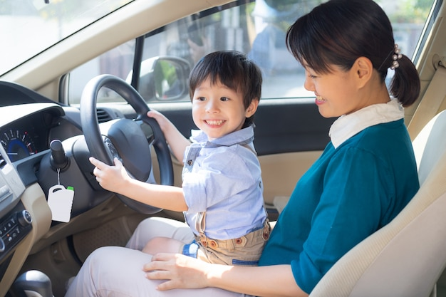 Mother and son enjoy to play with the steering wheel of car