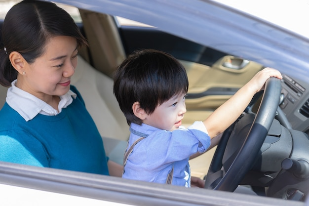 Mother and son enjoy to play with steering wheel