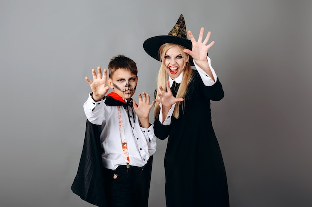 Mother and son in  fancy dress showing scary gesture at the camera. halloween
