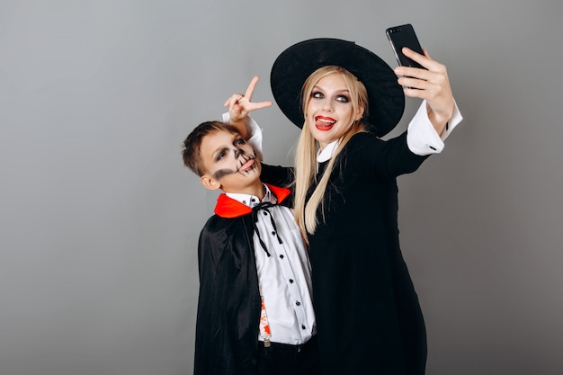 Mother and son in  fancy dress showing victory gesture and making selfie against