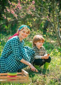 Mother and son farmers in the farm with countryside background eco farm happy family gardener carryi...