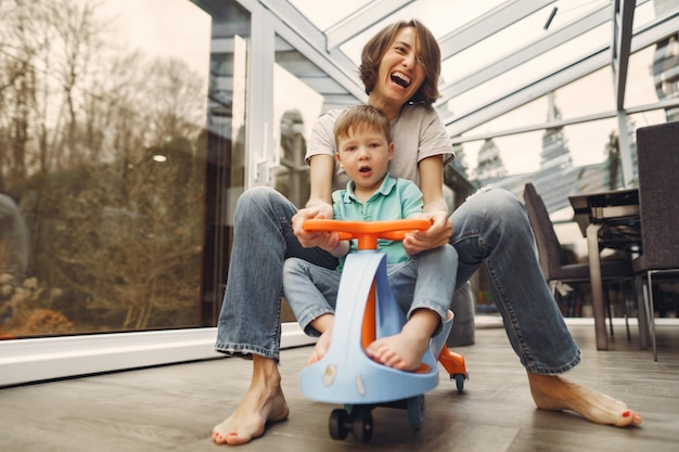 Mother and son go around the apartment on a toy car