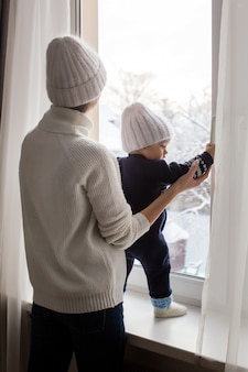 Mother and son in hats standing at the window in winter