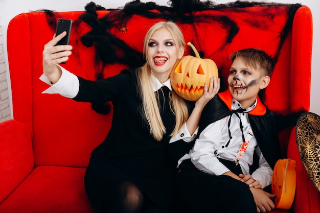 Mother and son have a funny time on red sofa and make a selfie closeup. emotion and halloween