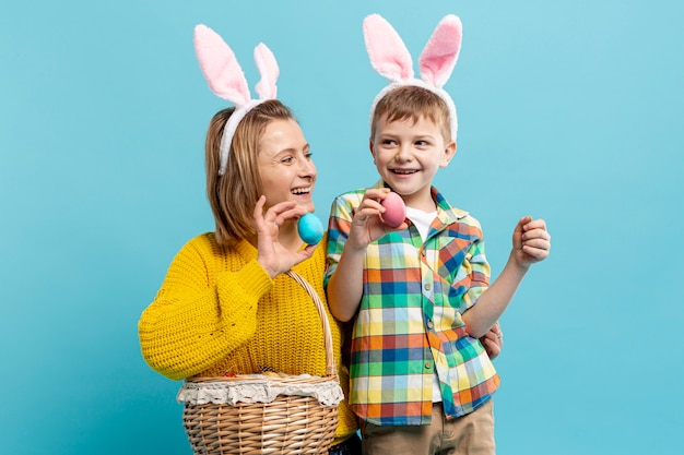 Mother and son holding basket of painted eggs