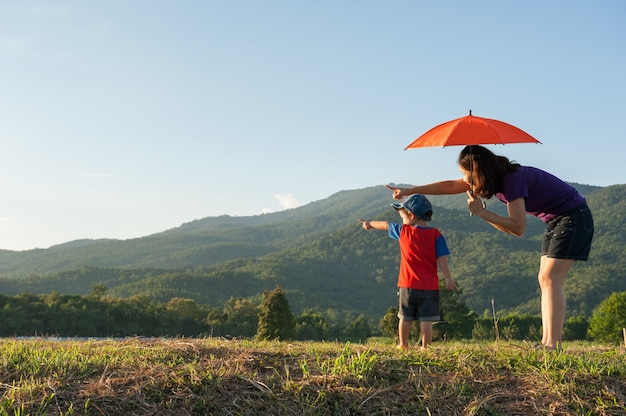 A mother and son holding umbrella outdoors at sunset