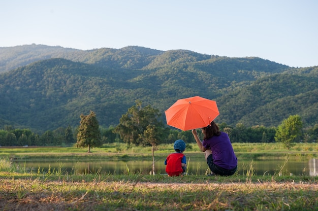 A mother and son holding umbrella and playing outdoors