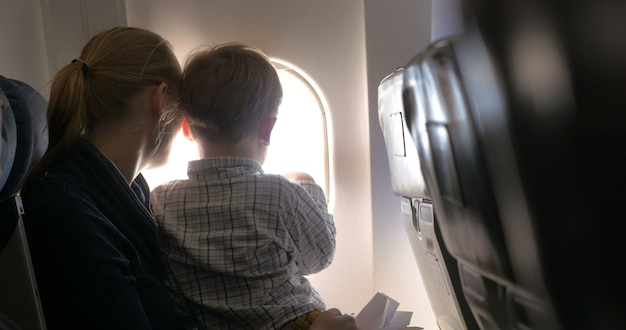 Mother and son looking out illuminator in plane