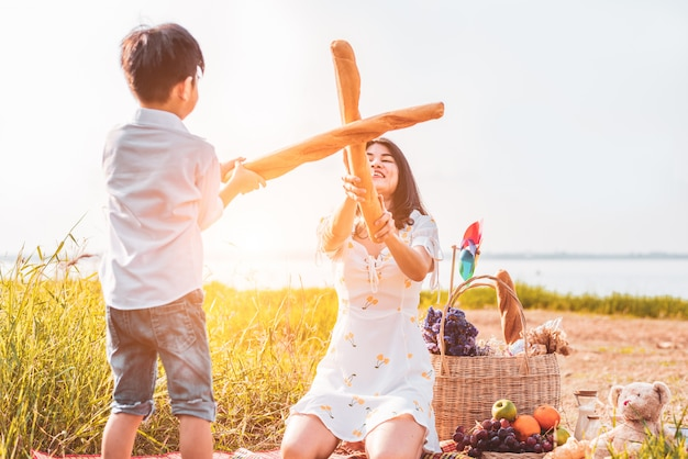 Mother and son play fencing with bread together when picnic at outdoors near lake or river