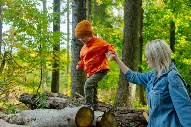 Mother and son playing on logs in a forest