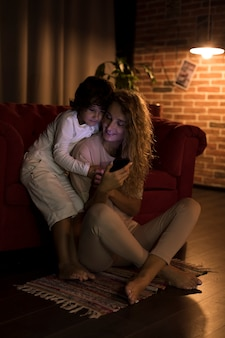 Mother and son playing on their phone