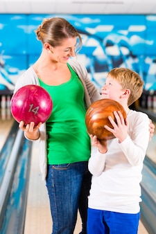 Mother and son playing together at bowling center