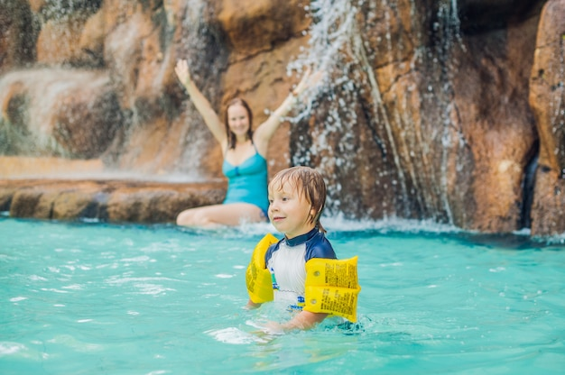 Mother and son relaxing under a waterfall in aquapark