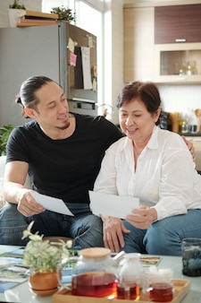Mother and son sitting on sofa and looking photos together while drinking tea at home