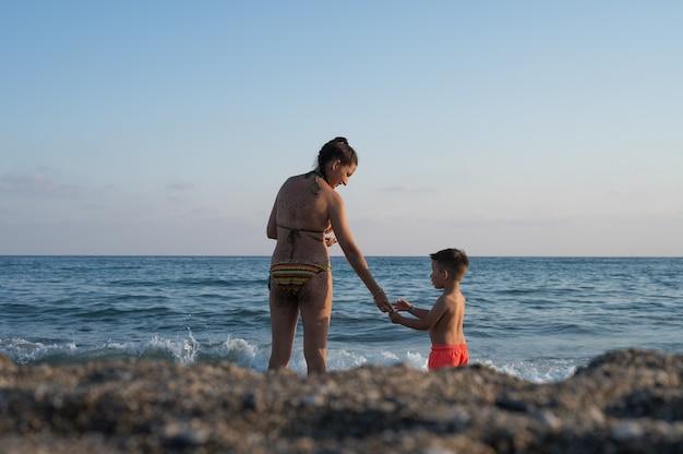 어머니 아들은 함께 바다 휴가를 보내고 있습니다. 자녀가 한 명 있는 가족입니다. 엄마와 행복한 어린 시절.