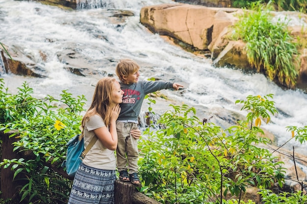 Mother and son on the surface of beautiful camly waterfall in da lat city,