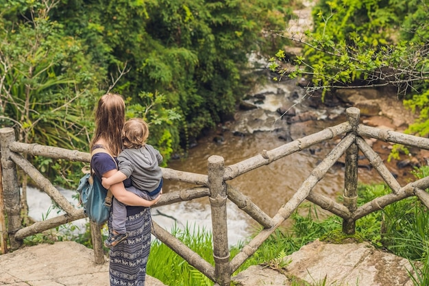 Mother and son in the surface of beautiful cascading datanla waterfall in the mountain town dalat, vietnam