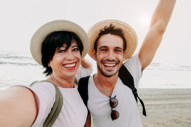 Mother and son taking a selfie at the beach with smartphone.