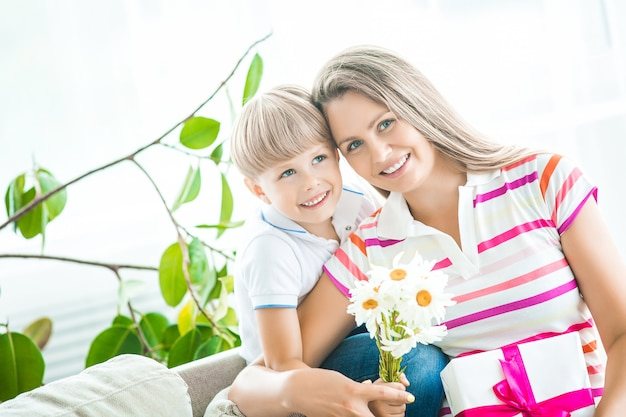 Mother and son together closeup portrait. mothers day picture with copy space. family indoors happy. smiling mom with her child holding present and flowers.