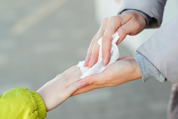 Mother and son using sanitizer spray for hands outdoors to prevent spread of germs, bacteria, coronavirus and virus.