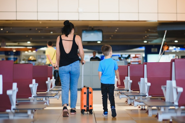 Mother and son waiting to board at departure gate of modern international terminal.