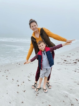 Mother and son walk along the foggy beach and take a photo on the phone. portrait of happy mom and child boy of cloudy weather made with phone. family time together.