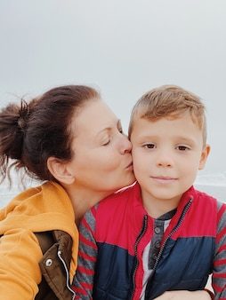 Mother and son walk along the foggy beach and take a selfie on the phone. portrait of happy mom kiss her child boy of cloudy weather made with phone. family time together.