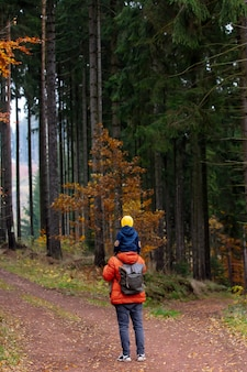 Mother and son walk through the forest in autumn
