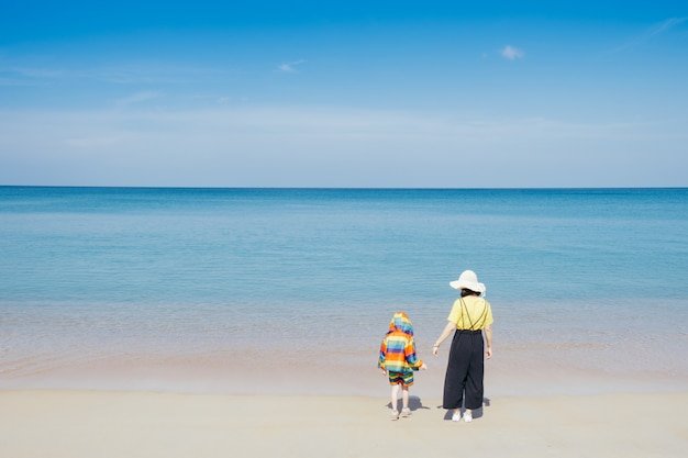 A mother and son walking on the beach and sea outdoors sea and blue sky