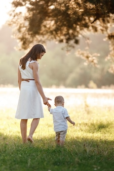Mother and son walking in the park on summer day