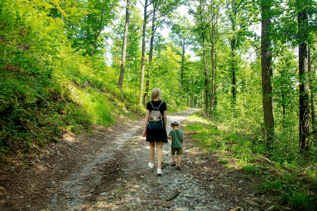 Mother and son walking on the road in forest