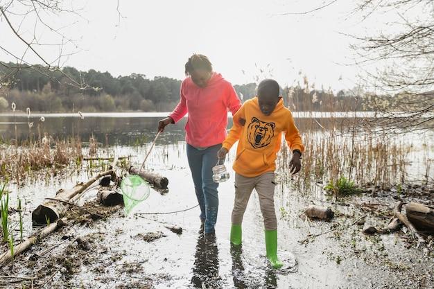 Madre e figlio che camminano in un luogo fangoso