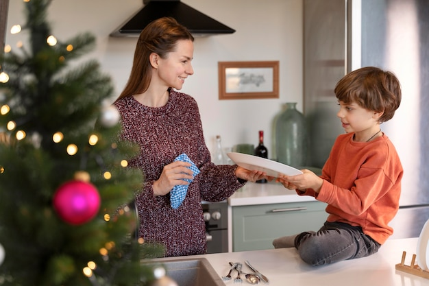 Mother and son washing the dishes together on christmas day