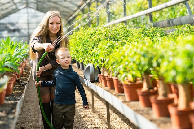 Mother and son watering potted plants in a greenhouse