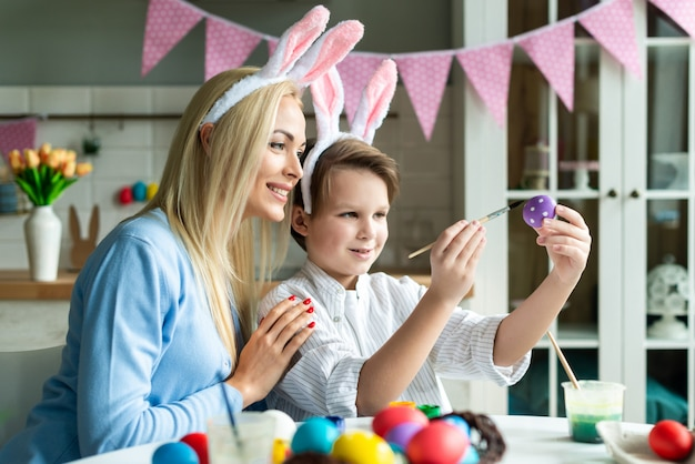 Mother and son wearing in bunny ears together preparing to easter and painting eggs.