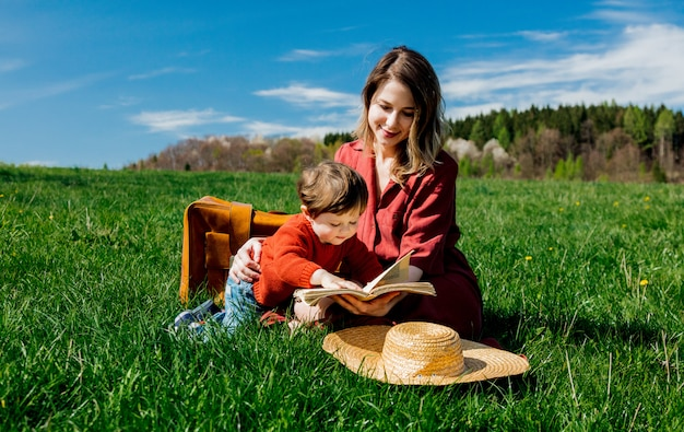 Mother and son with a book sitting on meadow.