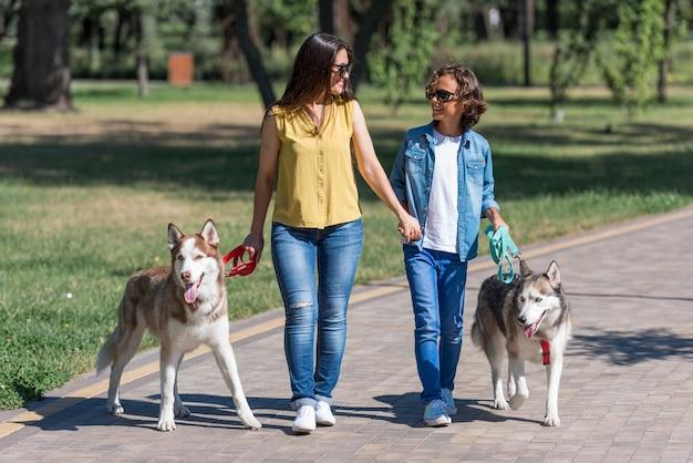 Madre e canzone che portano a spasso i loro cani al parco