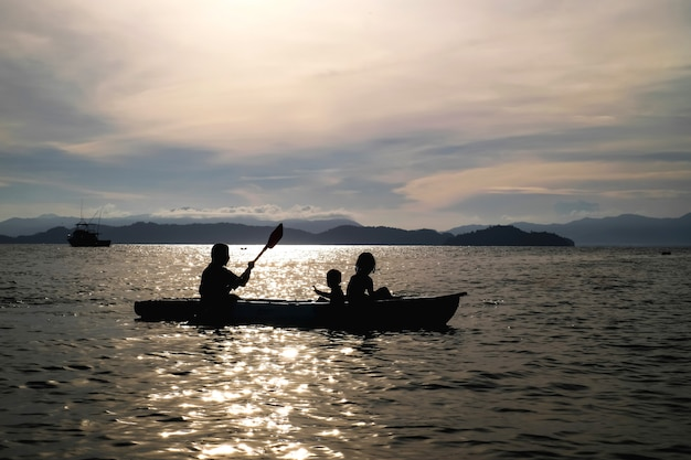 Mother and sons rowing kayak in the sea on vacation background is big mountain and sunset.