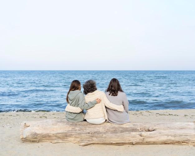 2 人の娘とビーチで過ごす母