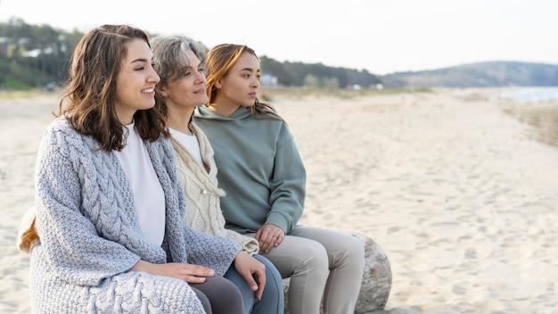그녀의 두 딸과 함께 해변에서 시간을 보내는 어머니