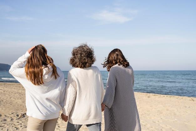 Мать проводит время с дочерьми на пляже