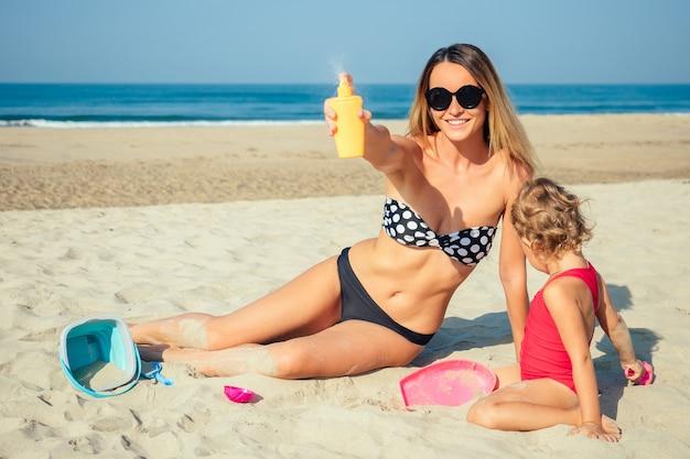 어머니는 해변에서 딸 옆에 자외선 차단제를 뿌립니다.