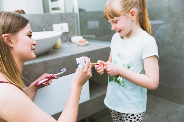 Mother squeezing paste on toothbrush of daughter