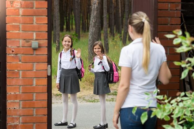 家の庭に立って、学校に歩いている娘たちに手を振っている母親