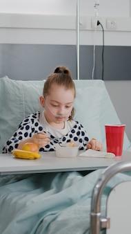 病棟で医療の専門知識を待っている昼食時に健康的な食事を食べながら病気の女の子と一緒に立っている母親。呼吸器疾患のある内科手術後に回復した入院中の少女